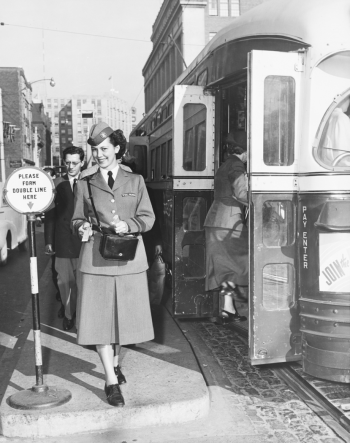 Uniformed women posing for the camera and offering a fare beside a streetcar.