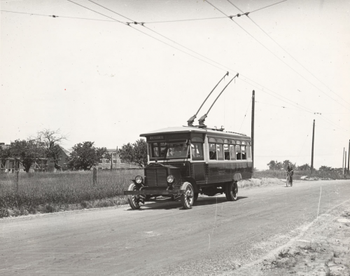 A bus is on a country road. There are metal arms coming up from the top of the bus to meet the electric wires overhead.
