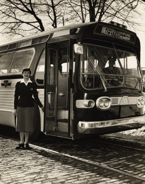 A woman in a TTC uniform consisting of a dark jacket and knee-length skirt stands beside the open door of a bus.