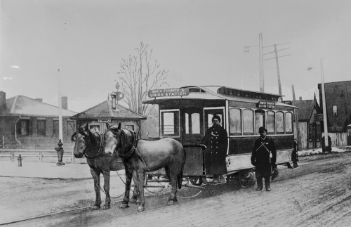 """Two horses pulling a small streetcar. The driver is wearing a large winter coat and is standing on the front step. The sign says """"North Toronto and Union Station."""""""