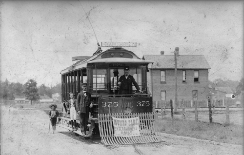 """A small electric streetcar. ON the front is a banner reading """"Munro Park, entertainment daily."""" A man in a driver's uniform stands on the the step, and another in the driver's platform at the front."""