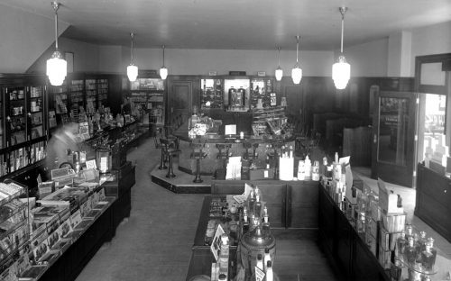 Inside a store containing many wooden shelves full of goods. In the background is a lunch counter surrounded by high chairs.