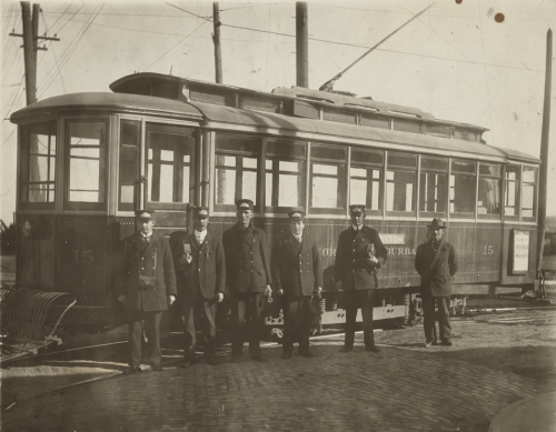 Men in uniforms standing in front of a streetcar.