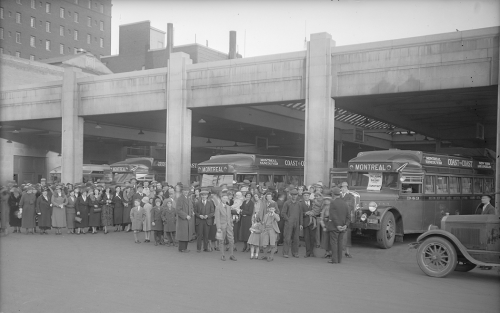 Several buses are parked in a half-open garage. Numerous people are posed in front of them and are looking at the camera.