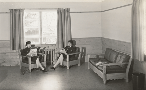 Two uniformed women seated by window reading magazines.