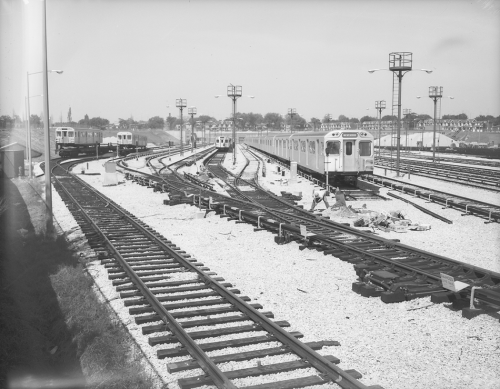 Subway cars on track in yard and other subway cars on flatbeds.