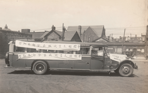 A long bus with banners written in Chinese on the side.