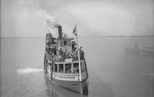 A small wooden ferry with an enclosed lower deck and people standing on the open upper deck.
