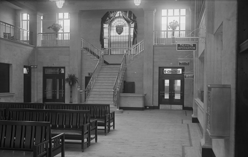 A waiting room filled with long wooden benches. In the background, a staircase leads up to a landing with a large arched window with the Grey Coach crest in it.
