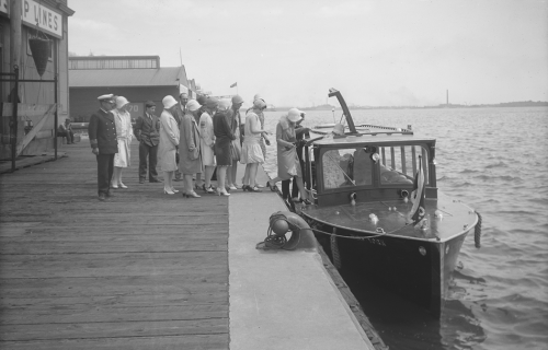 A group of people on a pier board a small boat with glass windows for sightseeing.