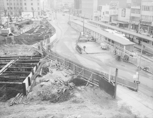 Excavation for tunnel and bus platforms in street. Storefronts line the far side of the street.