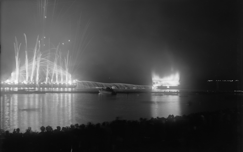 At night, a ship engulfed in flames floats on the water. There are fireworks going off beside it.