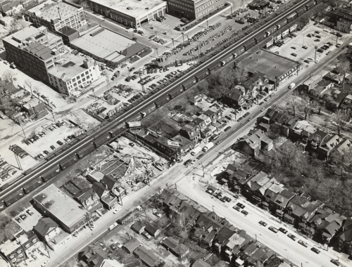 Work site surrounded by houses, parking lots, railroad tracks, and shops