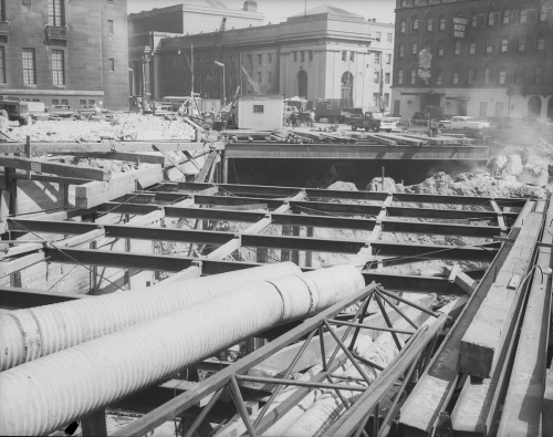 Beams laying over excavated area. Union Station and other buildings in background.
