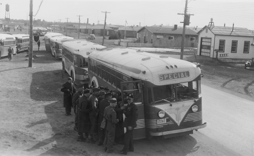 Uniformed men waiting to board lines of buses
