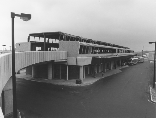 Station and bus waiting area with elevated track structure in place. Buses located at bus waiting area.
