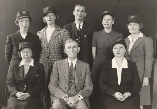 One man and two women seated with one man and four women standing behind. All of the women are wearing hats with TTC badges.