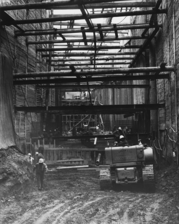 Heavy machinery and construction workers underground with hoarding and horizontal beams installed in tunnel