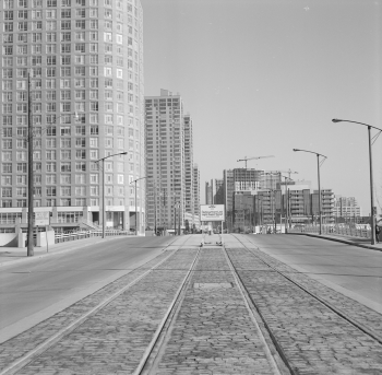 Two sets of newly installed streetcar tracks and sign advertising HLRT. Office towers and condominiums are in the background.
