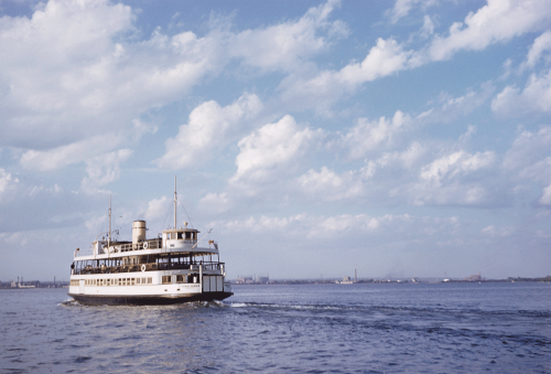 A large wooden ferry painted white chugs across blue water under a sky filled with fluffy white clouds.