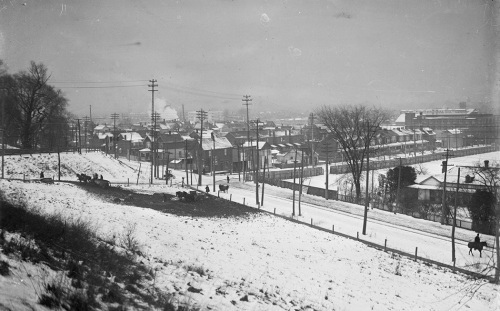 Looking down a hill to a road and houses beyond, all covered in snow.