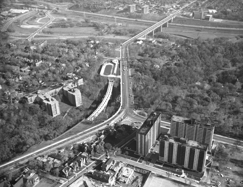 Apartment buildings and other buildings in foreground. Prince Edward Viaduct in background. Middle shows cars on Bloor Street and station structure