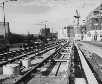 Newly installed track in unfinished right or way with motor vehicle traffic on roadway. Background shows condominiums.