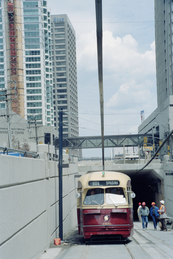 PCC streetcar emerging from tunnel with four construction men alongside checking its clearance.