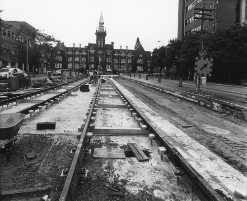 Newly installed streetcar tracks on right of way. Background shows the building at 1 Spadina Crescent.