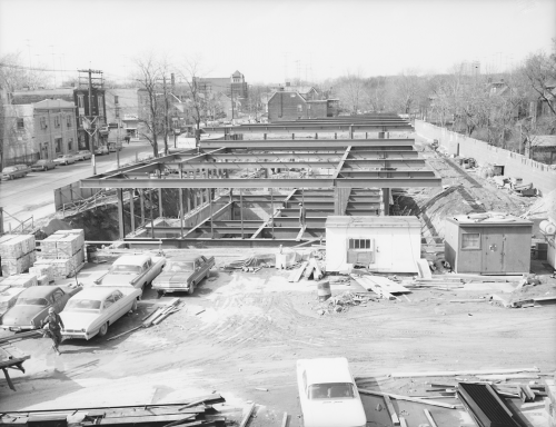 Structural beams erected prior to station construction. Foreground shows vehicles and workers trailers, background shows storefront lining street.