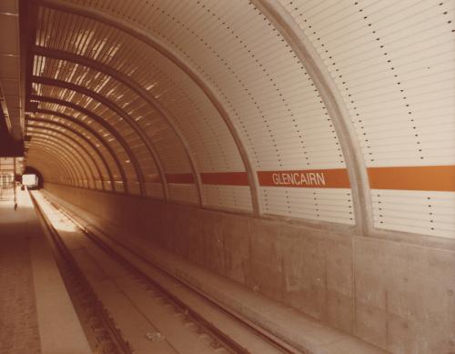 White tiled wall with orange banner of Glencairn Station.