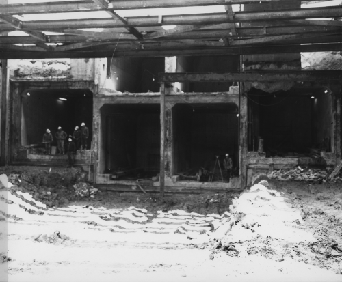 Six square tunnel structures. Four lower with group of workers standing in one and surveyor with equipment located in another.