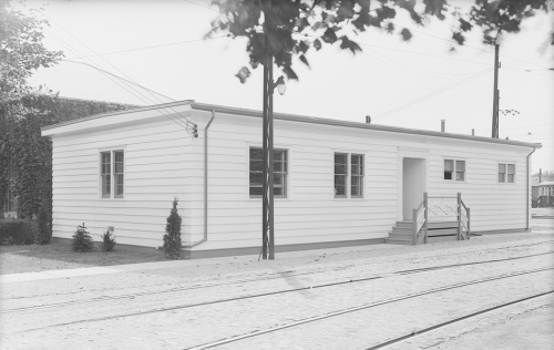 Perspective view of white one storey building near streetcar tracks.