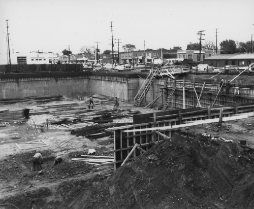 Works in excavated pit for station construction. Background shows storefronts.