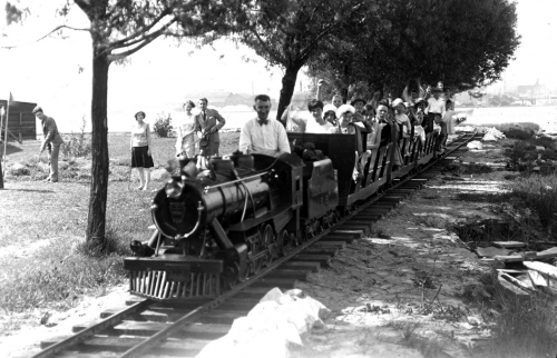 People are riding a miniature train with a small locomotive and open two-person cars.