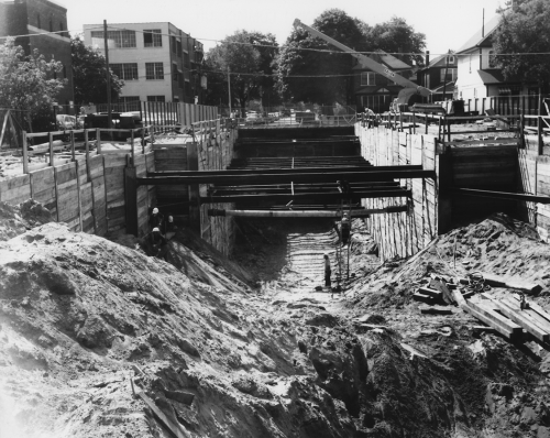 Cross section of excavated area and horizontal beams in place with houses and small buildings at street level