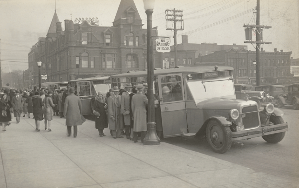 Men and women lined up to board bus. Background contains brick buildings.