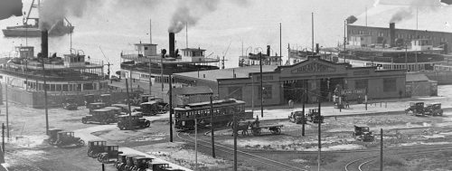 """A low building on the waterfront, with two large open doors and a peaked roof with a sign saying """"Hanlan's Point."""" Behind it in the water are two ferries with smoking smokestacks."""