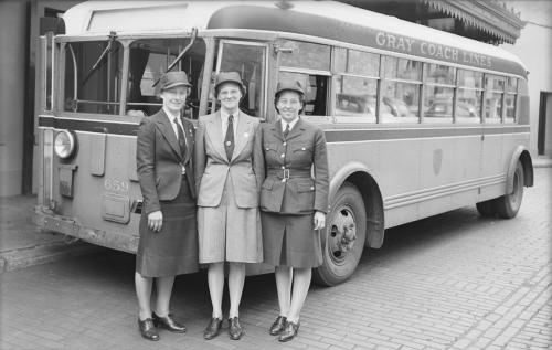 Three women in uniform standing near bus.