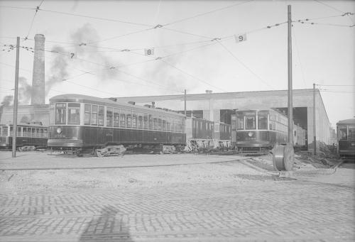 A row of streetcars on tracks outside the open doors of a one-storey garage.