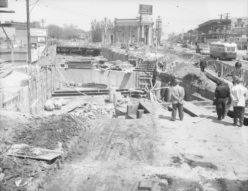 Construction workers looking toward excavated area construction and traffic along Bloor Street. Background shows bank and storefronts along road.