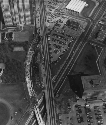 Aerial view of railway tracks, subway tunnel construction, and Bloor Street, includes subway station and parking lot.