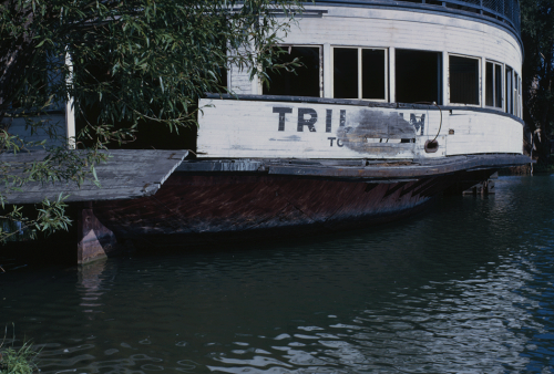 An old wooden ferry with its red and white paint fading is sitting in the water.