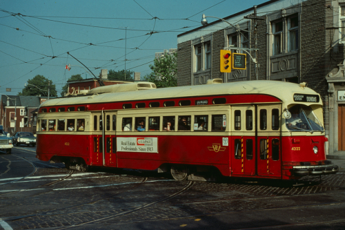 A red and cream coloured streetcar on the road.