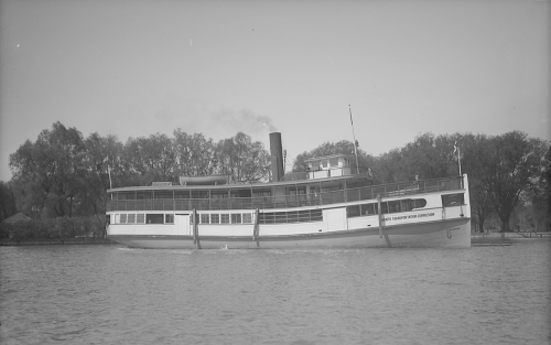 A large wooden ferry with an enclosed lower deck and an open upper deck.