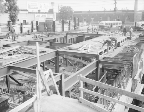 Street level with workers standing on partially installed mezzanine roof with PCC is background and one storey brick building