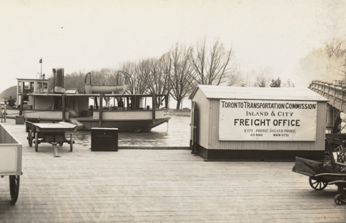 """A wide wooden dock with a ferry at the side and several carts waiting for freight. There is a small building with a sign that reads """"Island and City freight office."""""""