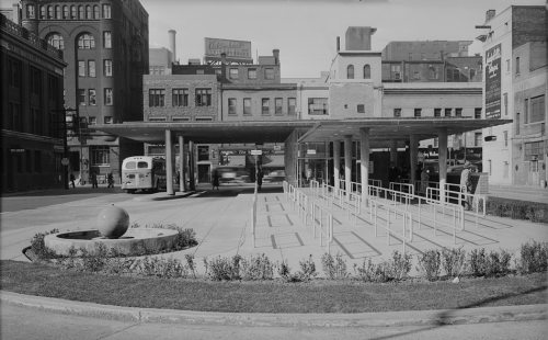 Foreground shows passenger waiting area and bus boarding location. Background shows station and buildings.