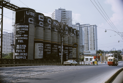 """A red and cream coloured streetcar drives past large concrete silos painted with the words """"Use Dominion Coal."""""""