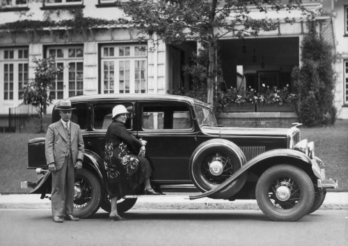 A well-dressed couple standing in front of a shiny automobile.